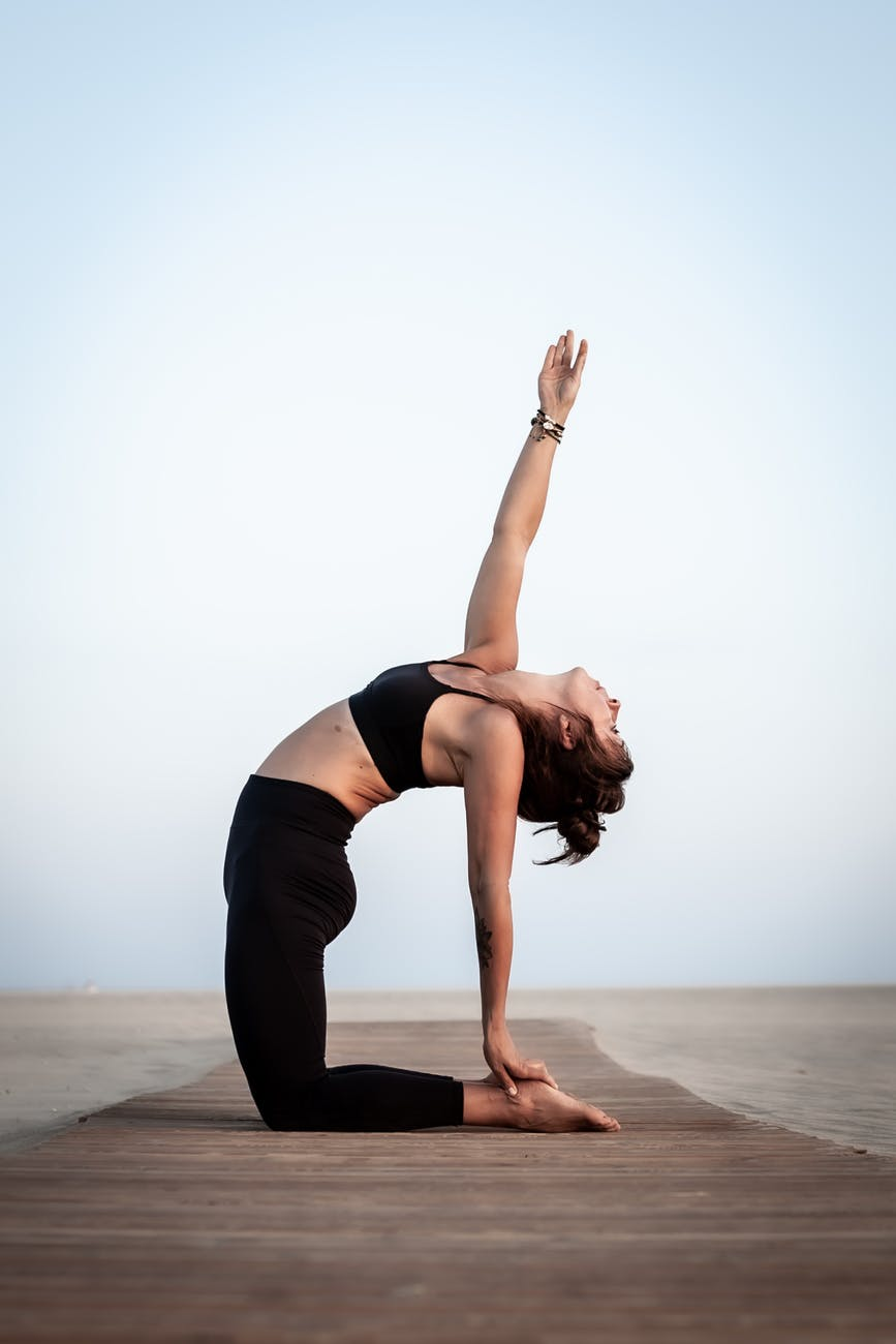 side view photo of woman doing yoga pose while kneeling on wooden footpath on the beach
