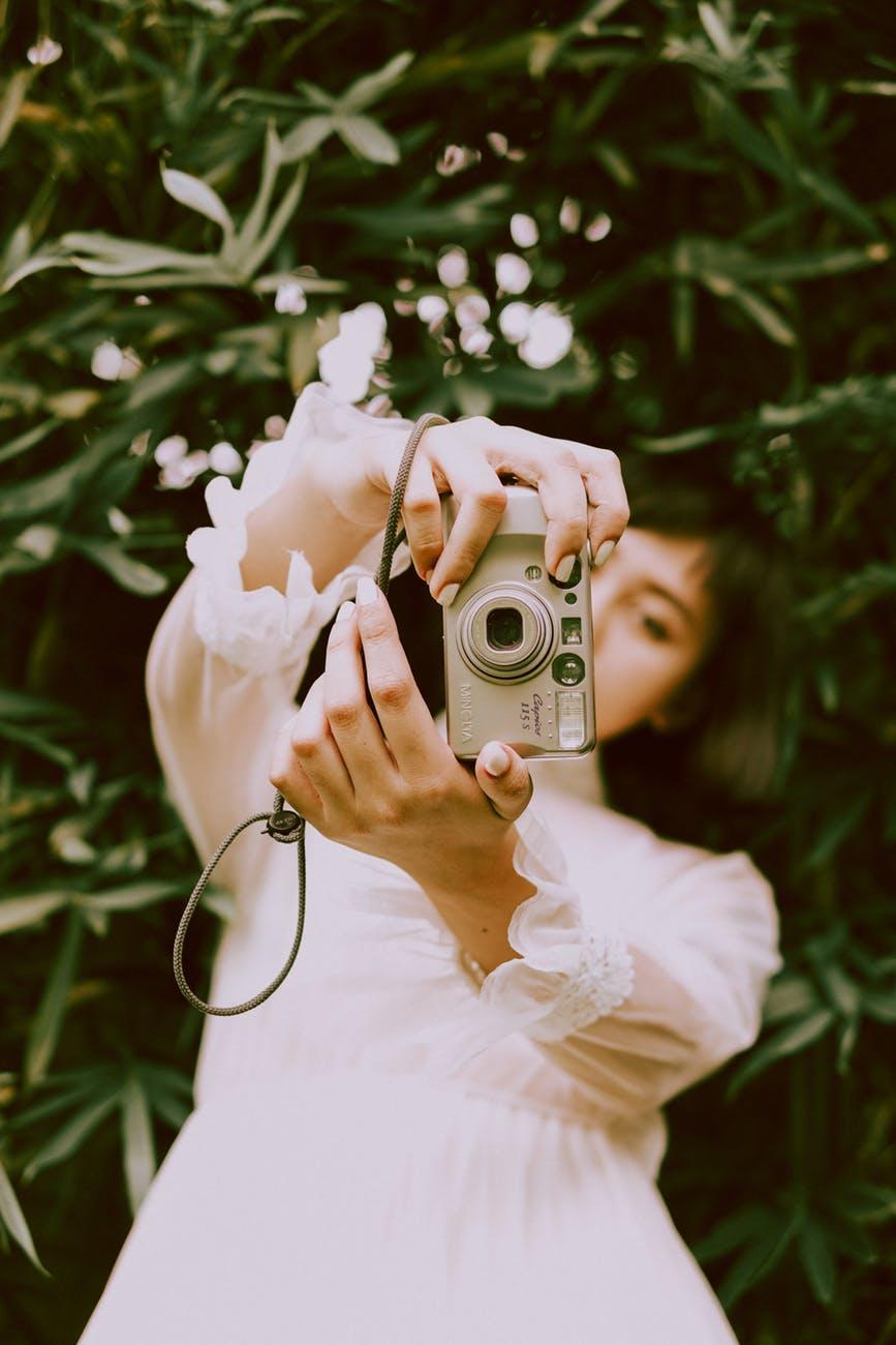 photo of woman holding camera